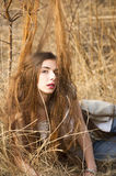 Girl having problem with her long hair. In high grass Stock Image