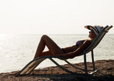 The girl having a rest on seacoast Stock Images