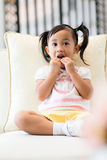 Girl having snack and sitting on couch Royalty Free Stock Photo