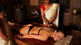 Girl having spa treatment. Two real Indian masseuses massage hands.