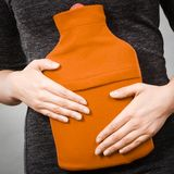 Girl having stomach ache, holding hot water bottle Royalty Free Stock Images