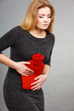 Girl having stomach ache, holding hot water bottle Royalty Free Stock Photography