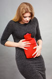 Girl having stomach ache, holding hot water bottle Stock Photos