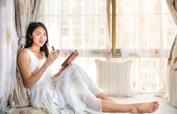 Girl having tea by a bay window Stock Photo