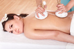Girl having Thai herb compress massage. Stock Photos