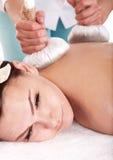 Girl having Thai herb compress massage. Girl having Thai herb compress massage in beauty spa. Body care royalty free stock photo
