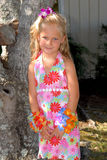 Girl In Hawaiian Dress. A beautiful little girl dressed in a tropical print dress with a flower in her hair and big blue eyes Royalty Free Stock Photography