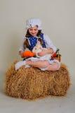 Girl in the hay feeding the Easter Bunny carrots. Stock Photos