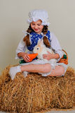 Girl in the hay feeding the Easter Bunny carrots. Royalty Free Stock Images