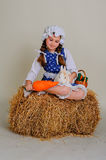 Girl in the hay feeding the Easter Bunny carrots. Stock Photo