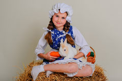 Girl in the hay feeding the Easter Bunny carrots. Stock Image