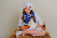 Girl in the hay feeding the Easter Bunny carrots. Stock Images