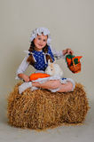 Girl in the hay feeding the Easter Bunny carrots. Royalty Free Stock Photography