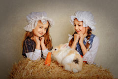 Girl in the hay feeding the Easter Bunny carrots. Girl in the hay feeding the Easter Bunny carrots Royalty Free Stock Image