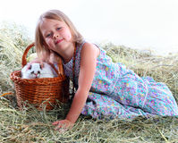 The girl on hay iron a favourite rabbit. Girl basket carrots hay rabbit hare weaving rod Stock Photos