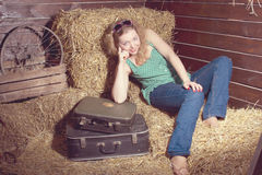 Girl in hay near the luggage Royalty Free Stock Photo
