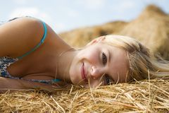 Girl on hay in summer Stock Photos