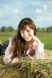 Girl on hay in summer Royalty Free Stock Image
