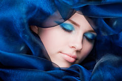 Girl head lying in blue silk Royalty Free Stock Images