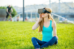 Girl in head-mounted display. Girl with pleasure uses head-mounted display in park Royalty Free Stock Photography