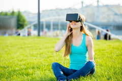 Girl in head-mounted display. Girl with pleasure uses head-mounted display in park Royalty Free Stock Photos