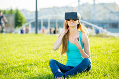 Girl in head-mounted display. Girl with pleasure uses head-mounted display in park Stock Photography