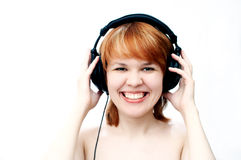 Girl in head-phones. Red-haired girl in head-phones Royalty Free Stock Images