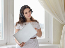 Girl with the head-phones working in a laptop Stock Photos