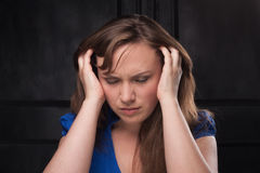 Girl with headache on dark background. She clasped head in her hands. Close-up Stock Images