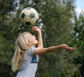 Girl heading with soccer ball Royalty Free Stock Image