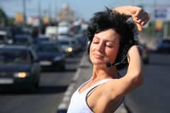 Girl in headphone set on highway middle Royalty Free Stock Images