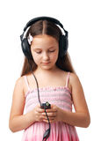 Girl with Headphones. Young girl with headphones looking at something in her mobile or player Royalty Free Stock Photography