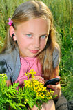 Small girl listening to music on telephone with he. Adphones on a meadow Stock Image