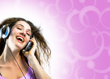 Girl in headphones. On a pink background stock images