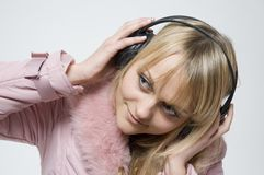 Girl with headphones. On is looking off to the side Stock Photography