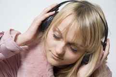 Girl with headphones. On is facing sideways with eyes closed Stock Photos