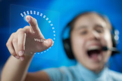 The girl in headphones adjusts the volume. Girl in headphones adds volume to maximum Royalty Free Stock Photography