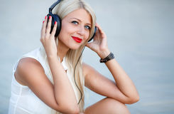 Girl with headphones on a blue background. Beautiful young woman with long blond hair and grey eyes,red lips,large black headphones,wearing a white sleeveless stock photo