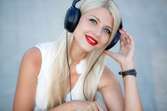 Girl with headphones on a blue background. Beautiful young woman with long blond hair and grey eyes,red lips,large black headphones,wearing a white sleeveless stock photography