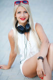Girl with headphones on a blue background. Beautiful young woman with long blonde hair and grey eyes,red lipstick,large black headphones,dressed in a white royalty free stock photos