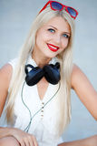 Girl with headphones on a blue background. Beautiful young woman with long blonde hair and grey eyes,red lipstick,large black headphones,dressed in a white stock photos