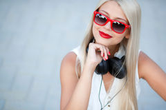 Girl with headphones on a blue background. Beautiful young woman with long blonde hair and grey eyes,red lipstick,large black headphones,dressed in a white stock photography