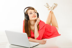 Girl with headphones and computer listening to music. Leisure free time, music, online and internet concept - happy teenage girl with headphones and laptop Royalty Free Stock Photos