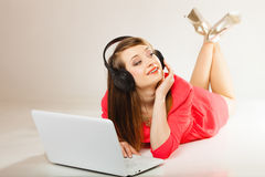 Girl with headphones and computer listening to music Stock Photography
