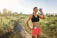 Girl in headphones drinking water after jogging Royalty Free Stock Image
