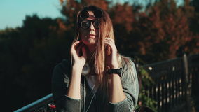 The girl with headphones and funky glasses in a city park. stock video