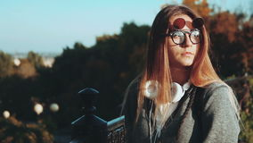 The girl with headphones and funky glasses in a city park. stock footage