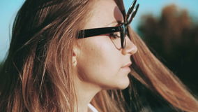The girl with headphones and funky glasses in a city park. stock video footage