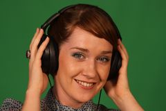 Girl in headphones. Girl with headphones on green background Royalty Free Stock Images