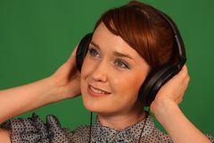 Girl in headphones. Girl with headphones on green background Stock Photography